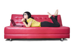 Female model with laptop daydreaming on sofa. Picture of beautiful female model lying on the sofa while daydreaming with a laptop computer, isolated on white Stock Image