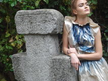 Female model leaning on traditional stone cross Stock Images