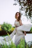 Female model in long beige dress posing dynamic in the beach. waving fabric. fluttering long skirt Stock Image