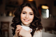Female model with long hair. Amazing sensual girl with gorgeous make-up is enjoying a delicious coffee or tea, playfully Royalty Free Stock Photography