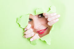 Female model looking thru ripped green cardboard Royalty Free Stock Photography