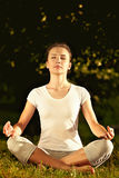 Female model meditating in serene harmony in lotus position in park. Royalty Free Stock Photo