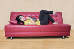 Female model with a novel on sofa Stock Images