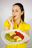 Female model with plate with fruit. Gorgeous brunette female model with plate full of fruit Royalty Free Stock Photo