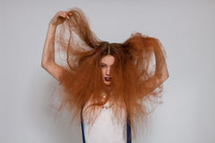 Female model playing with frizzy hair Royalty Free Stock Photography