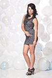 Female model posing with a balloon background. Caucasian female posing in a grey cocktail dress in front of a white and blue balloon wall Stock Photo