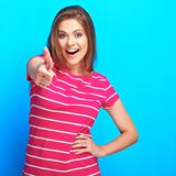 Female model posing in studio against blue background showing Royalty Free Stock Images
