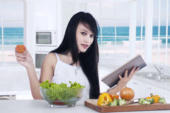 Female model reads book and make salad Stock Image