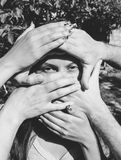 Female Model with several Hands on Her Face. In black and white Royalty Free Stock Photos