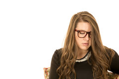 Female model sitting looking down wearing glasses Royalty Free Stock Photos