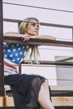 Female model sitting at a railing in a t-shirt with the American Stock Images