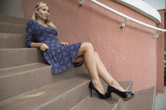 Female model sitting on stairway wearing dress and heels Royalty Free Stock Photo