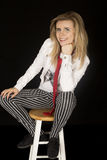 Female model sitting on stool wearing striped pants smiling Stock Images