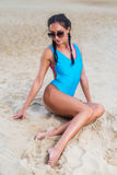 Female model with slender body wearing swimsuit sitting alone on sandy beach. Female model with slender body wearing swimsuit sitting alone on sandy beach Royalty Free Stock Photos