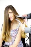 Female model smiling getting long hair straightened in studio Stock Image