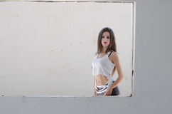 Female model standing behind of a cement window Royalty Free Stock Image