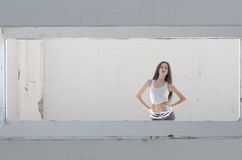 Female model standing behind of a cement window Royalty Free Stock Images