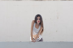 Female model standing behind of a cement window Stock Images