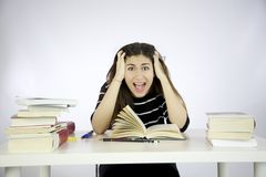 Female model studying shouting. Girl studying book on a desk shouting Stock Image
