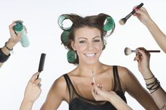 Female Model Surrounded With Hands Holding Cosmetics Stock Image