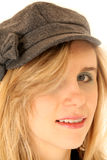 Female model wearing a gray hat with her hair down in her eye Royalty Free Stock Image