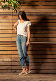 Female model wearing t-shirt and jeans on wooden background Stock Photos