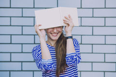 Female model with a white book on the background wall Royalty Free Stock Image