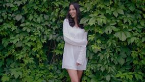 Female model in white tunic dress with green leaves on background stock video