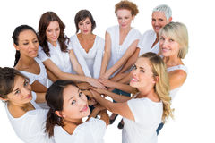 Female models joining hands in a circle and looking at camera Stock Images