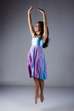 Female modern dancer. Beautiful female modern jazz contemporary style dancer on a grey background. Dancer is barefoot and wearing a blue and purple dress royalty free stock image