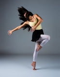 Female modern dancer. Beautiful female modern jazz contemporary style dancer on a grey background. Dancer is barefoot and wearing a yellow leotard, black skirt stock photos