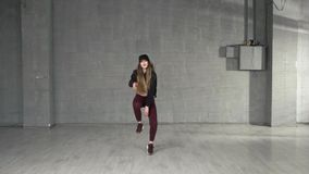 Female modern style dancer dancing in studio. Young beautiful athletic woman dancing modern style dance hip-hop on studio on wall background stock video
