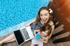 Close-up of female mother, daughter and laptop on background of swimming pool. Female mother, daughter and laptop keyboard on sunny day background of swimming Royalty Free Stock Photo