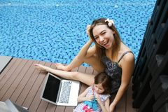 Close-up of female mother, daughter and laptop on background of swimming pool. Female mother, daughter and laptop keyboard on sunny day background of swimming Royalty Free Stock Photography