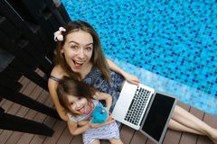 Close-up of female mother, daughter and laptop on background of swimming pool. Female mother, daughter and laptop keyboard on sunny day background of swimming Stock Photo