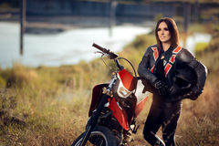 Female Motocross Racer Next to Her Motorcycle. Portrait of a cool sports woman in off road adventure stock image