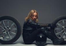 Female with motorcycle helmet sitting between two car wheels. Stock Photo