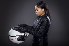Female Motorcycle Rider or Racer with Helmet. Black female motorcycle rider or race car driver wearing a racing helmet and leather jacket. Part of the gritty royalty free stock image