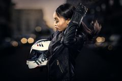 Female Motorcycle Rider on a Street. Black female motorcycle rider or race car driver wearing a racing helmet and leather jacket. Part of the gritty woman series royalty free stock photo