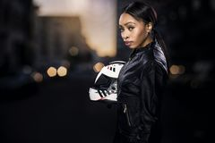 Female Motorcycle Rider on a Street. Black female motorcycle rider or race car driver wearing a racing helmet and leather jacket. Part of the gritty woman series royalty free stock photos