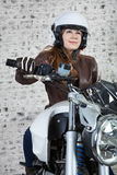 Female motorcyclist in open helmet holds steering wheel while sitting on the motorbike Stock Photography