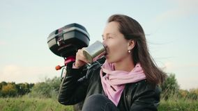 Female motorcyclist traveler coffee on vacation on a cliff. Tourist relaxes in nature on the background of motorcycle stock video