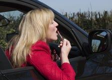 Female motorist applying makeup Royalty Free Stock Image