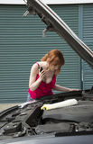 Female motorist looking into the engine bay on her car Royalty Free Stock Photos