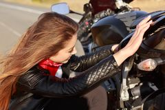 Female motorist tries to solve problem with transport, repairs motorbike during trip, fixes some parts, stops on road, being talen. Ted biker. Repairing vehicle stock photo