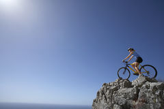 Female mountain biker sitting on bicycle at edge of rock in sunlight, looking at horizon over sea Royalty Free Stock Photos
