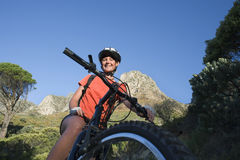 Female mountain biker sitting on bicycle in valley, smiling, portrait, low angle view Royalty Free Stock Photos