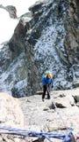 Female mountain climber rappelling off a high alpine peak in the Swiss Alps above Zermatt stock photo