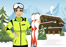 Female mountain skier standing in front of chalet in winter ski resort. Female mountain skier standing in front of a chalet in winter ski resort Royalty Free Stock Photography