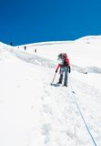 Female mountaineer ascending a glacier. Stock Photos